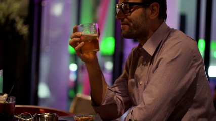 Young man drinking beer sitting in cafe at night