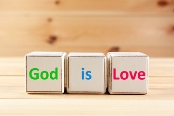 God is Love text spelled in cubes on wooden background
