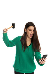 Furious lady breaks smartphone with hammer. Isolated on white