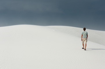 Man hiking in White Sands National monument, NM