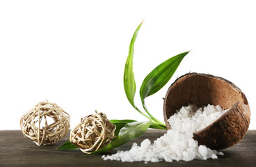Coconut shell of sea salt with wicker balls and green petals