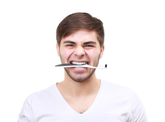 Portrait of smiling young man with toothbrush isolated on white