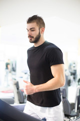 Handsome young man exercising on a treadmill at the gym