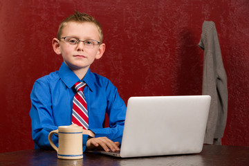 Young working boy with tie and grown up glasses on computer.