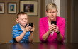 Mother and young son on mobile cell phones texting.