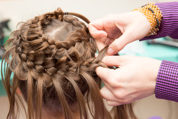 hairdresser weaves an unusual hairstyle child