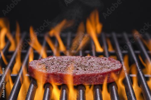 Hamburger Patty on a Hot Flaming BBQ Grill - 78291899
