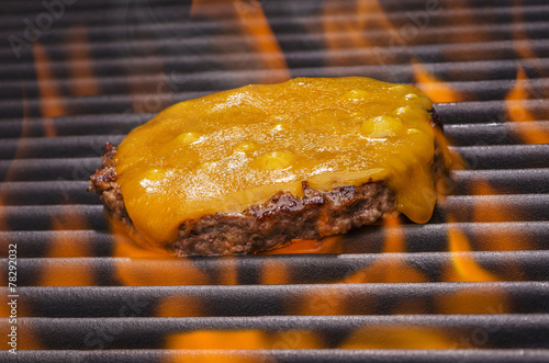 Tuinposter Grill / Barbecue Cheeseburger on a Hot Flaming BBQ Grill