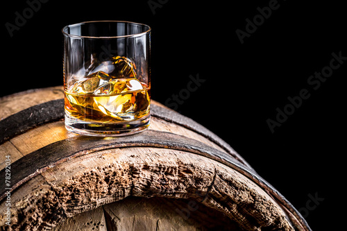 Leinwanddruck Bild Glass of whisky with ice on old wooden barrel