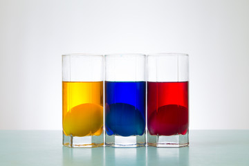 Easter eggs in red yellow blue color liquid