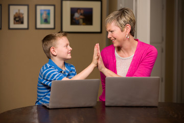 Family of happy mother and young son on computers.