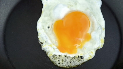 Sunny-side egg cooking in frying pan