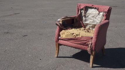Retro Ragged Armchair Outside On Asphalt