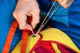man tighten the valve of parachute backpack closeup