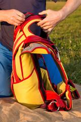man packs parachute in  knapsack outdoor