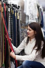 woman  chooses  belt at shop