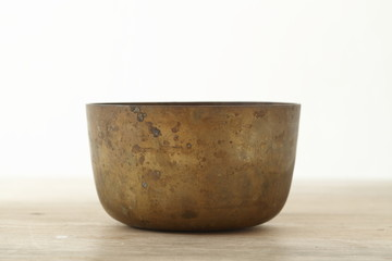 Old brass bowl on wooden table