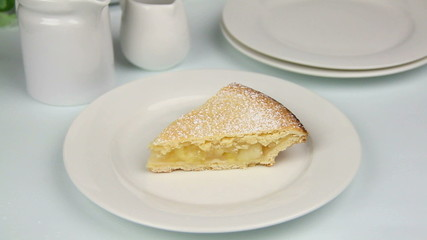Slice of apple pie with cream poured over it.