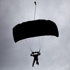 dark silhouette of man on parachute in sky