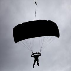 dark silhouette of man on parachute in sky