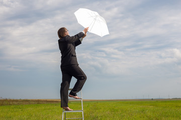 man  with white umbrella on stepladder in field goes in sky