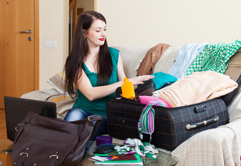 brunette woman packing suitcases