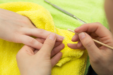 remove cuticles with wooden stick on  background  towels