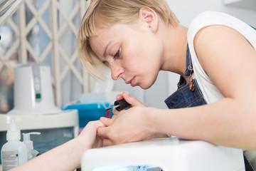 blonde manicurist paints client  nails