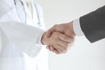 握手する医師とビジネスマン