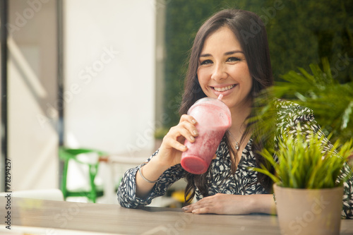 Hispanic girl drinking a smoothie - 78294257
