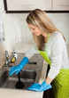 Blonde woman cleaning pipe with plunger