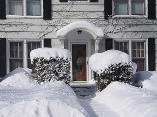 house with snow covered front yard