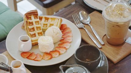 Waffle serving with ice cream and strawberry