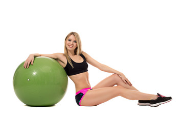 Smiling athletic woman posing with fitness ball
