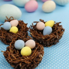 Springtime chocolate nests filled with Easter eggs on blue