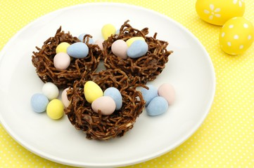 Springtime chocolate nests filled with Easter eggs on yellow