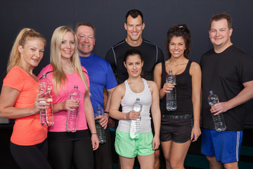 Fitness Group having a bottle of water and smiling to the camera