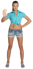 Pretty girl in shorts and shirt showing stop hand sign. Full