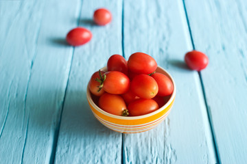 Red cherry tomatoes in bowl on blue wooden background