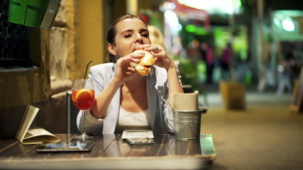 Young, pretty woman eating sandwich sitting in cafe at night