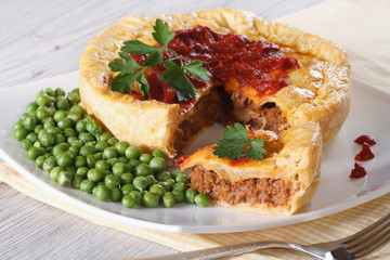 Meat pie and green peas on a plate. horizontal