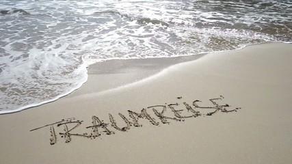 Wort Traumreise am Strand wird von Wellen weggespült