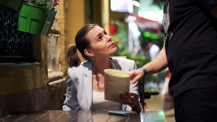 Young woman placing order to waiter in cafe at night