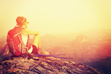 woman hiker enjoy the view at on mountain peak rock
