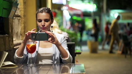 Young woman taking photo of cocktail with cellphone in cafe
