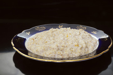 Oatmeal in a beautiful plate on a black background