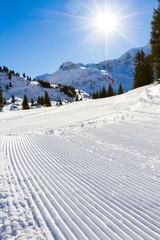 freshly groomed winter alpine ski slope