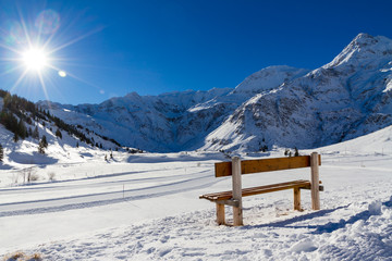 inviting bench to sit on a mountain sun in Alps