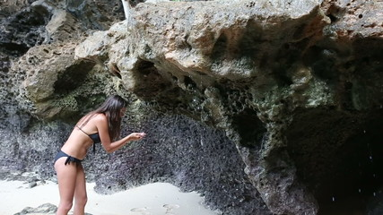 brunette girl in black bikini washes under cliff and go away