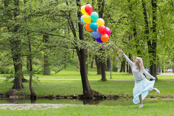 Happy young woman with colorful balloons in park